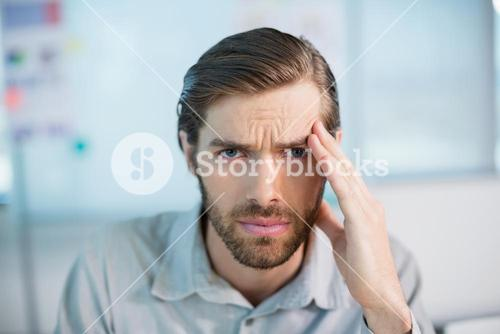 Tense business executive sitting with hand on forehead