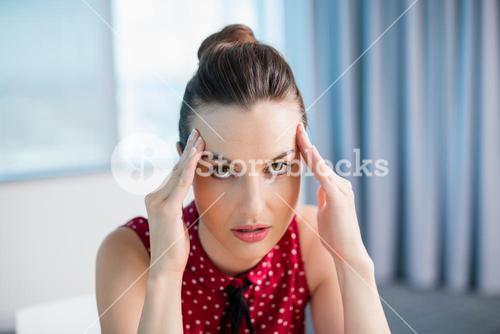 Tense female business executive sitting with hand on forehead