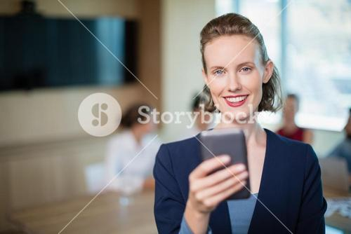 Beautiful business executive talking on her mobile phone in conference room