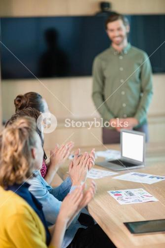 Business team applauding their colleague in conference room