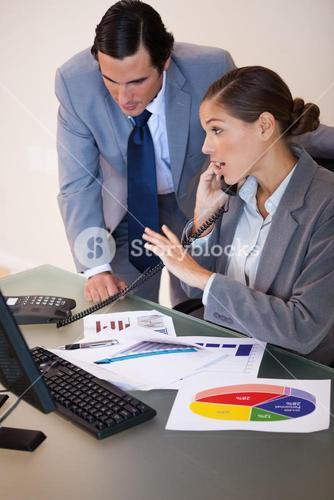 Businesswoman getting a phone call while analyzing statistics