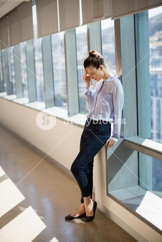 Tense female business executive leaning near window