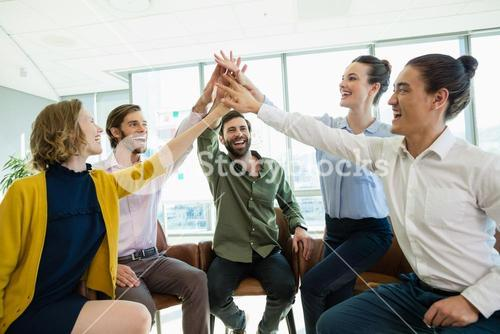 Business executives giving high five to each other