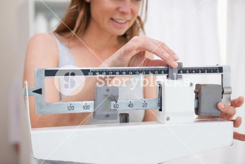 Woman adjusting scale