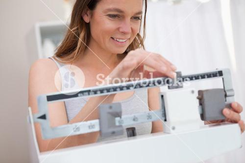 Woman adjusting medical scale