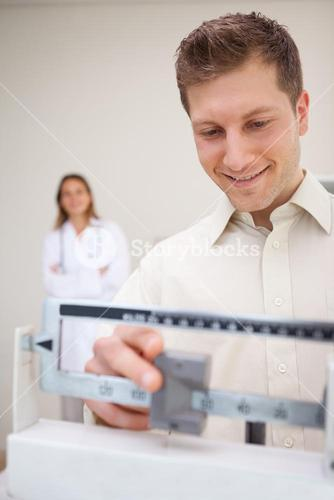 Man adjusting scale while being supervised