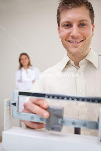 Smiling man adjusting scale