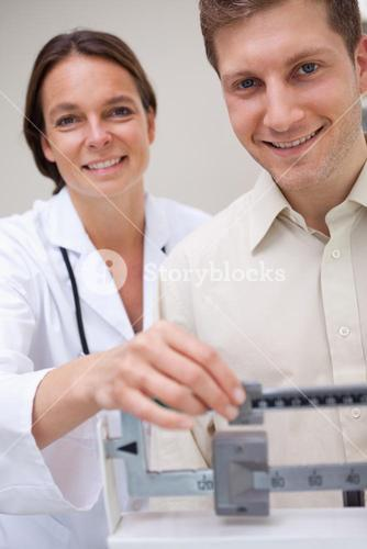Doctor measuring patients weight