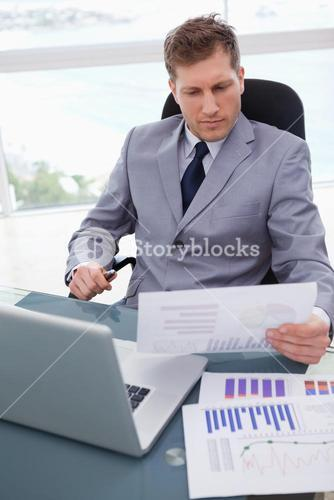 Businessman with market research results leaning back