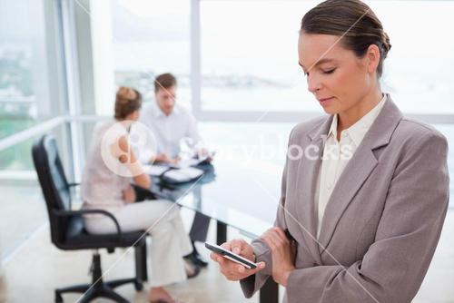 Standing real estate agent with cellphone
