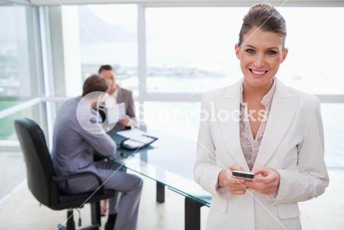 Smiling marketing manager holding cellphone