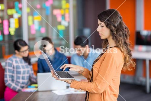 Attentive female graphic designer using laptop