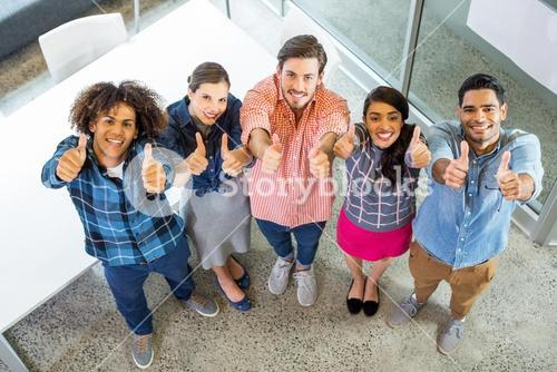 High angle view of happy executives showing thumbs up