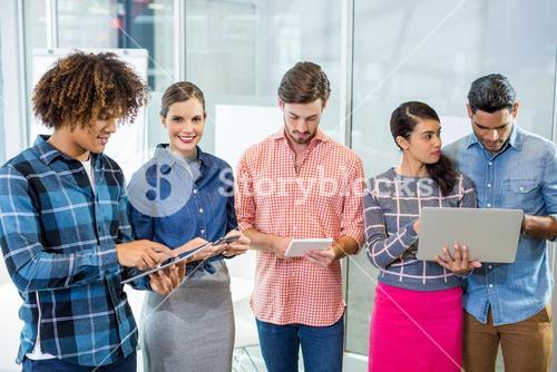 Executives using laptop, digital tablet and mobile phone