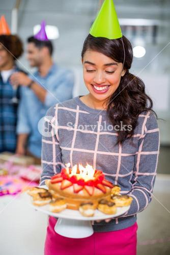 Happy female executive wearing party hat and holding birthday cake