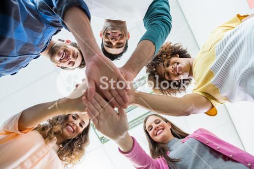 Team of smiling executives forming hand stack