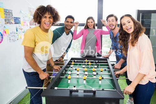 Happy graphic designers playing table football