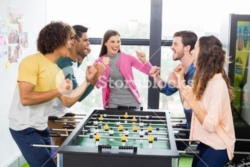 Happy executives cheering while playing table football
