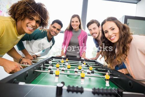 Happy executives playing table football