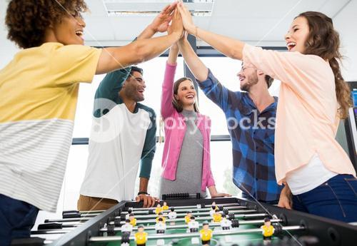 Executives giving high five while playing table football