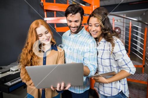 Happy male and female executives using laptop