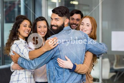 Portrait of smiling executives forming circle in office
