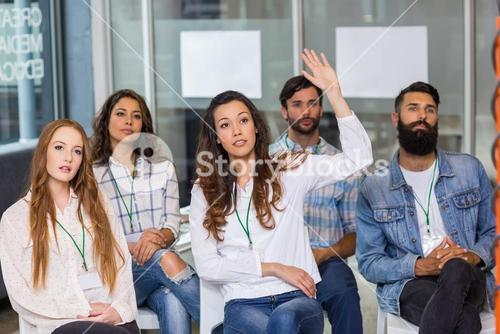 Female executive raising hand during presentation
