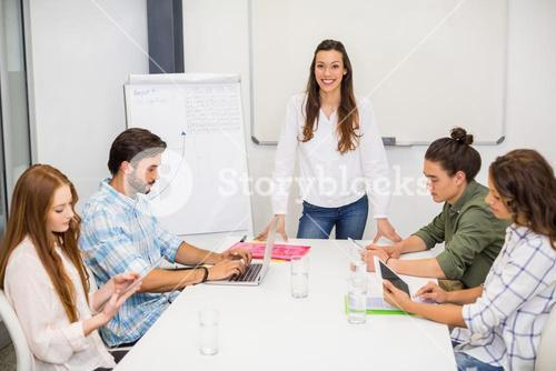 Attentive executive using laptop and digital tablet in conference room