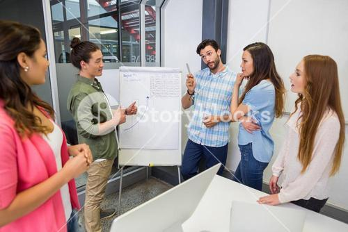 Team of executives having discussion over flip chart