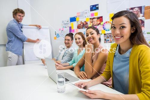 Portrait of smiling executives sitting in conference room during meeting