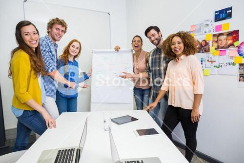 Smiling executives discussing over flip chart board in conference room meeting