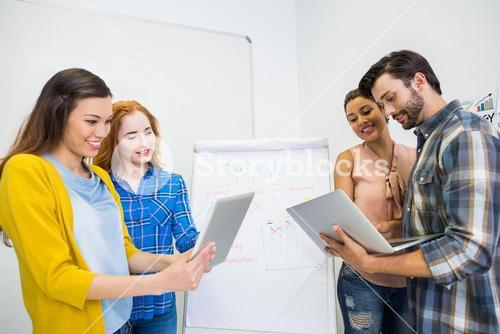 Smiling executives discussing over digital tablet and laptop in conference room meeting
