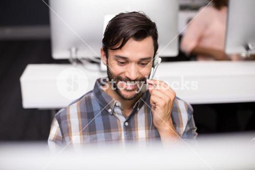 Smiling male customer service executive talking on headset at desk