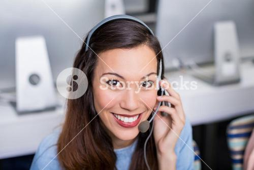 Portrait of female customer service executive talking on headset at desk