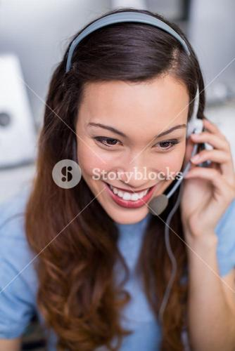 Smiling female customer service executive talking on headset at desk