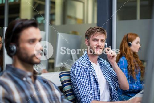 Portrait of male customer service executive talking on headset at desk