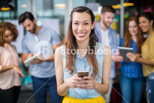 Portrait of smiling female executive using mobile phone