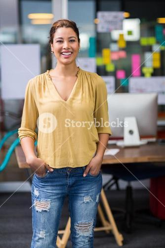Portrait of smiling female executive standing with hands in pocket