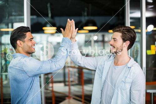 Two colleagues giving high five in office