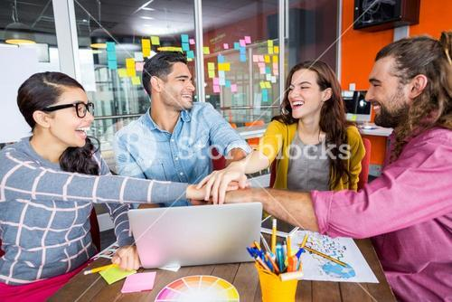 Smiling graphic designers with their hands stacked together in meeting