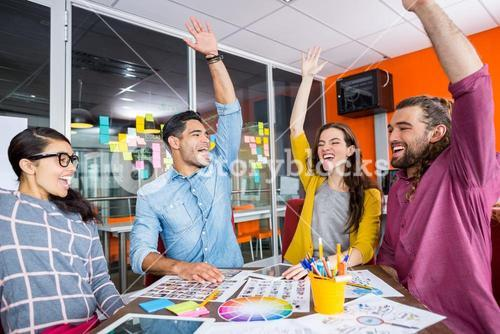 Smiling graphic designers with their hands raised together in meeting