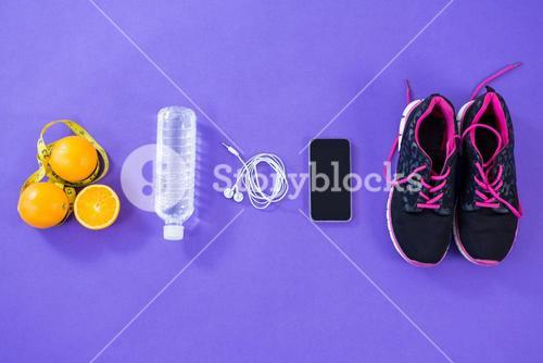 Mobile phone with earphones, shoes, water bottle, lemon and measuring tape