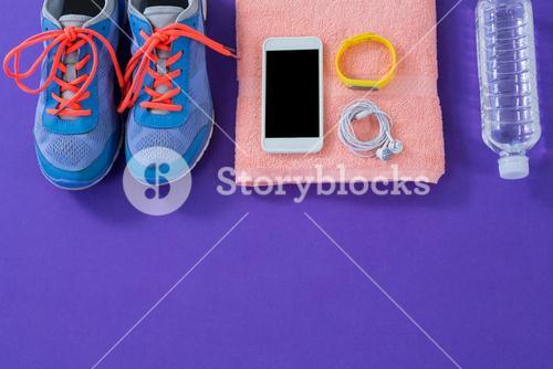 Sneakers, water bottle, towel, mobile phone with headphones and wristband