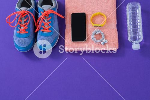 Sneakers, water bottle, towel, mobile phone with headphones and fitness band