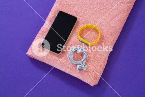 Towel with mobile phone, headphones and fitness band