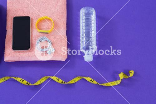 Water bottle, towel, measuring tape, mobile phone with headphones and fitness band