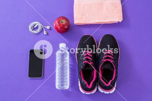 Sneakers, water bottle, towel, mobile phone with headphones and apple