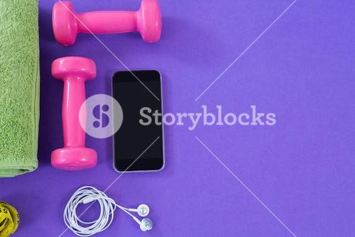 Dumbbells, towel, mobile phone with headphones