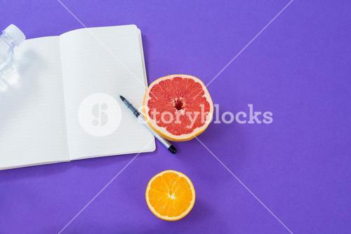 Grapefruit, lemon with opened book and pen