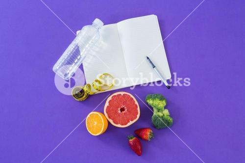 Water bottle, measuring tape, various fruits, vegetable, opened book and pen